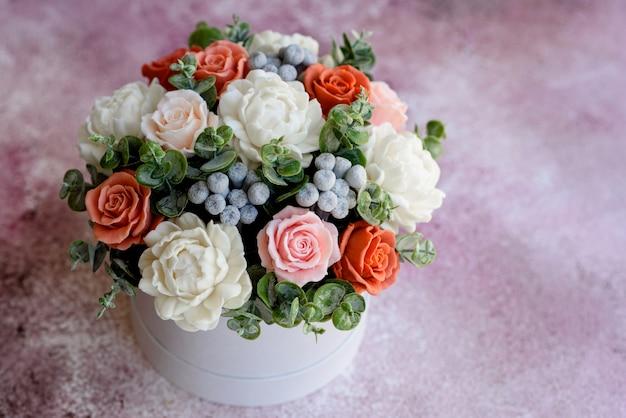 ギフトの円筒形の段ボール箱に美しい明るいバラの花の花束。石鹸の花のギフトブーケ Premium写真