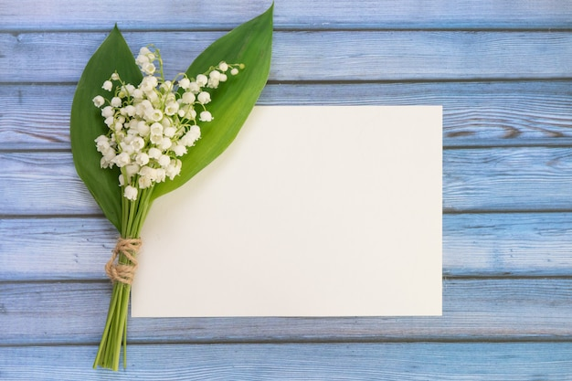 Букет цветов рядом с пустым листом бумаги Premium Фотографии