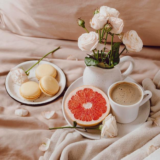 Букет цветов с утренним кофе и грейпфрутом на кровати Бесплатные Фотографии