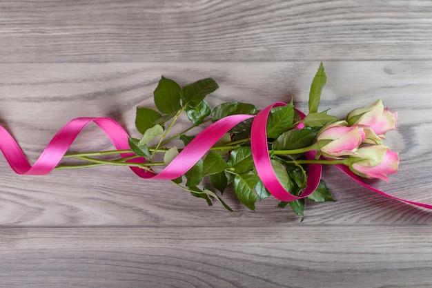 木の上のリボンで包まれたピンクのバラの花束 無料写真