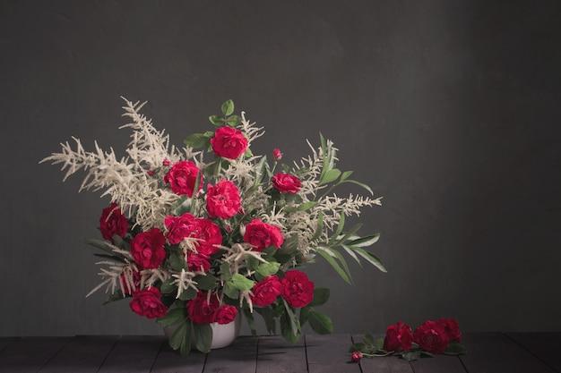 Букет из красных роз на фоне черной стене Premium Фотографии