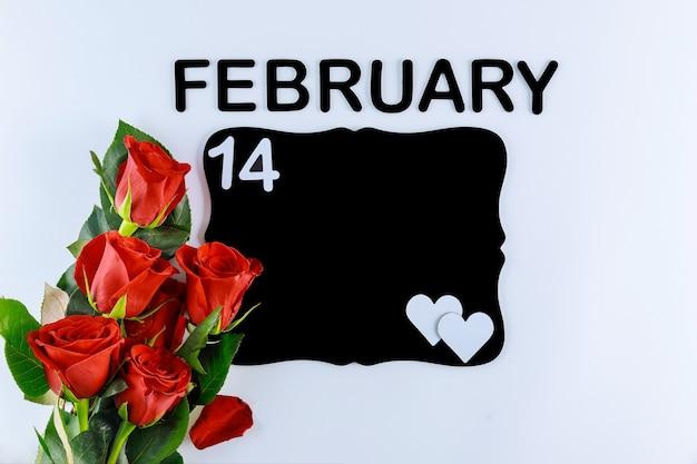 テキスト2月14日と白い背景で隔離のモックアップ黒板と赤いバラの花束。母の日またはバレンタインデー。 Premium写真