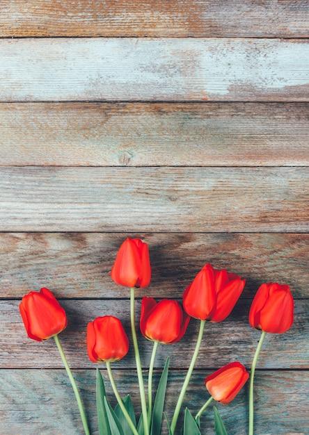Copyspaceと水色の木製レトログランジに赤いチューリップの花束。 Premium写真