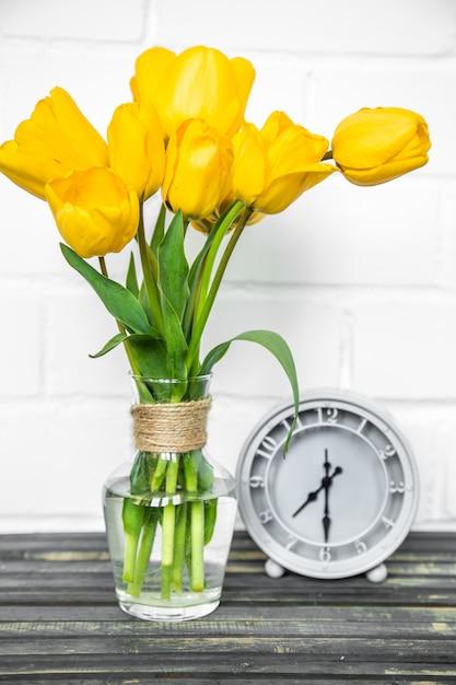 Букет из желтых тюльпанов и ретро-часы Бесплатные Фотографии