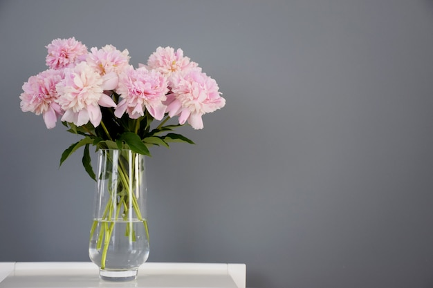 Premium Photo Bouquet Of Pastel Pink Peony Flowers In Bloom In Glass Vase On White Table On Gray Wall Background
