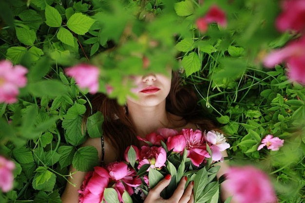 Bouquet of peony. beautiful young woman lies among peonies. holidays and events. valentine's day. spring blossom. Premium Photo