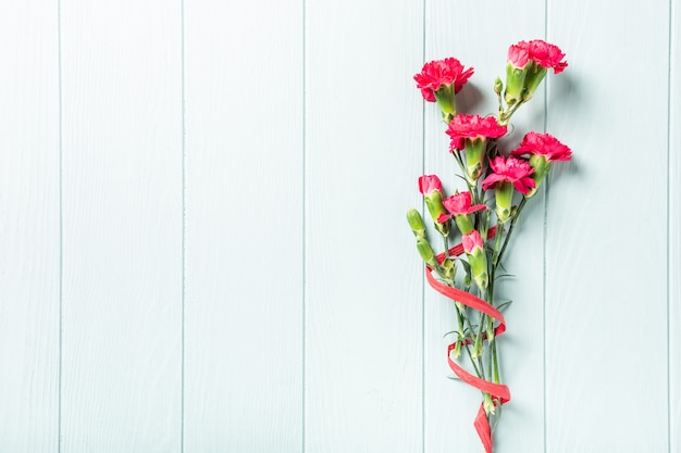 Bouquet of pink carnation on light turquoise wooden background Premium Photo