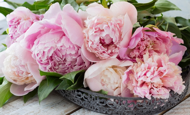 A bouquet of pink peonies on a wooden table in an old vase Premium Photo