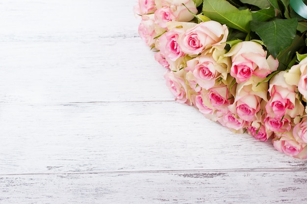 Bouquet of pink roses with blue ribbon on a vintage wooden background Free Photo