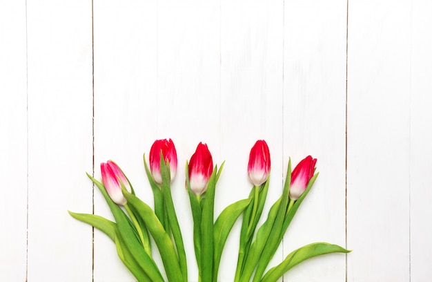 Bouquet of pink tulips on a white rustic wooden background