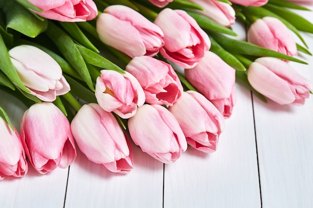 Bouquet of pink tulips on white wood Premium Photo