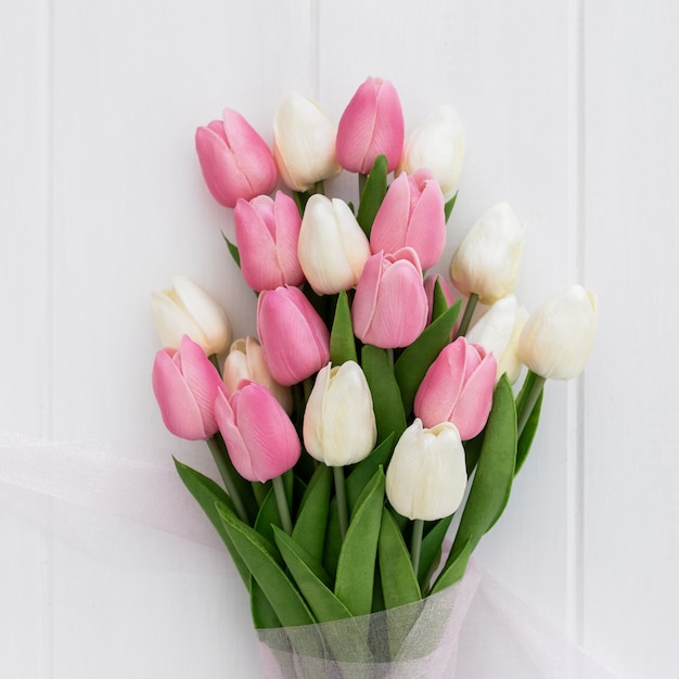 Bouquet of pretty pink and white tulips on wooden background Free Photo
