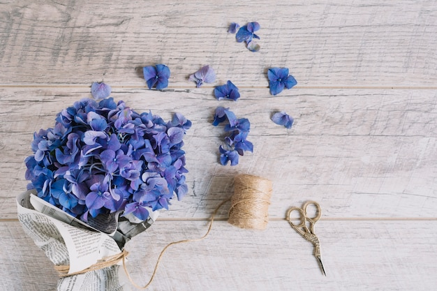 Bouquet of purple hydrangea flowers wrapped in newspaper with scissor on wooden table Free Photo