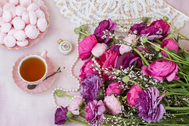 A bouquet of ranunculus, a cup of tea, meringue, a fan and a bottle of perfume Premium Photo
