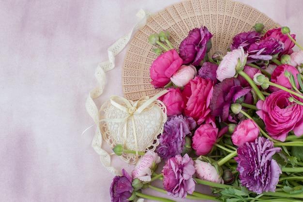 A bouquet of ranunculus fan, heart of lace, lace ribbon Premium Photo