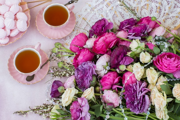 A bouquet of ranunculus, two cups of tea and meringue Premium Photo
