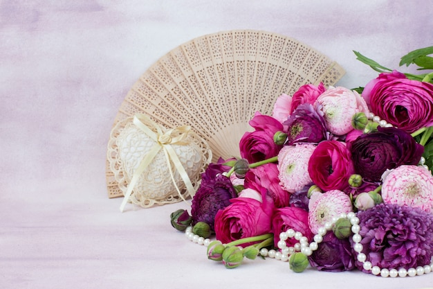 A bouquet of ranunculuses, a fan, a heart of lace and pearl beads Premium Photo