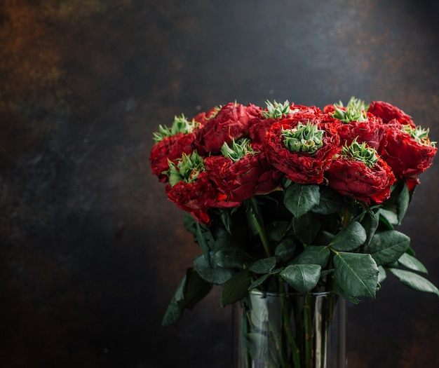 Bouquet of red flowers in glass vase in dark background Free Photo