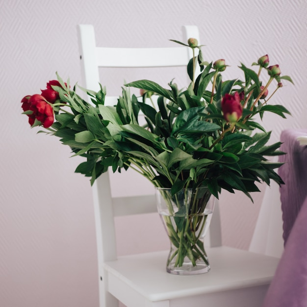 Bouquet of red peonies in a vase on the white chair, wedding decoration Premium Photo