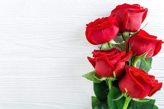 Bouquet of red roses on white wooden background. Premium Photo