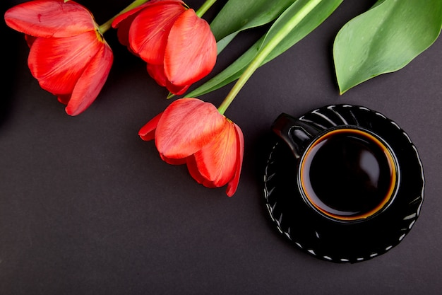Bouquet of red tulips and cup of coffee Premium Photo