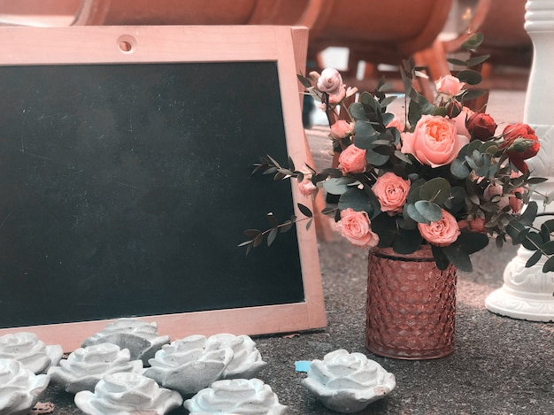 A bouquet in a rustic style with a frame and a black board for drawing a place for text Premium Photo