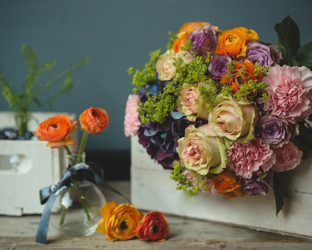 A bouquet and single autumn flowers around on the table Free Photo