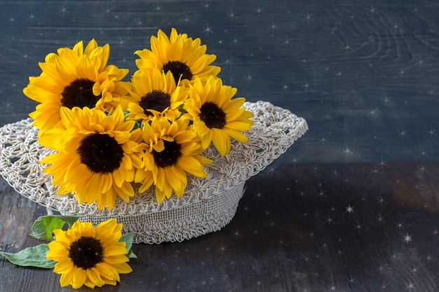 Bouquet of sunflowers in a straw hat Premium Photo