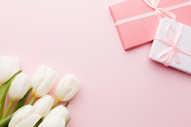 Bouquet of tulip flowers and gifts on pink background Free Photo