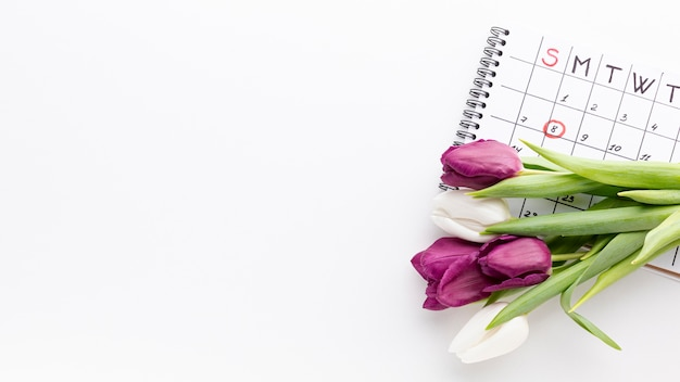 Bouquet of tulips next to calendar with copy space Free Photo