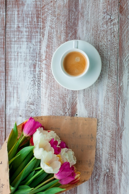 The bouquet of tulips is wrapped in a paper isolated on a wood background Premium Photo