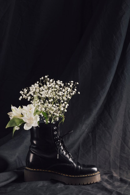 Bouquet of white blooms in dark leather boot Free Photo