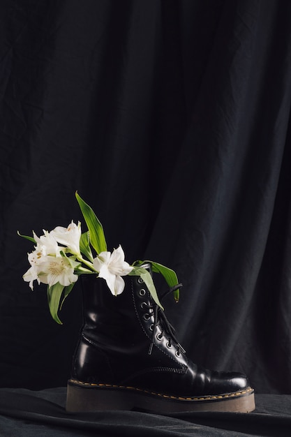 Bouquet of white blooms with green leaves in dark boot Free Photo