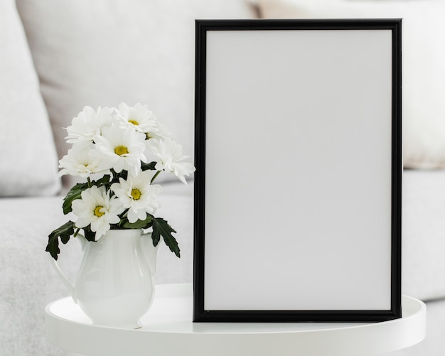 Bouquet of white flowers in a vase with empty frame Free Photo