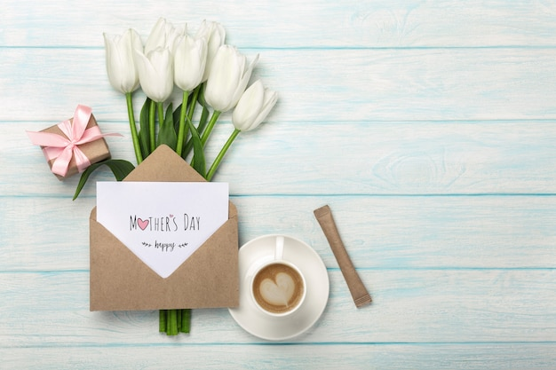 A bouquet of white tulips, cup of coffee, gift box with a love note and envelope on blue wooden boards . mother's day Premium Photo