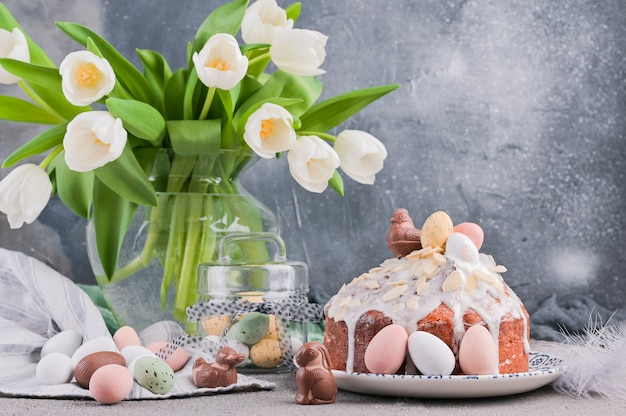 Bouquet of white tulips and easter cupcake on a gray background. Premium Photo