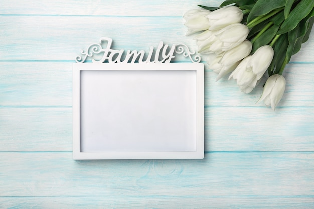 A bouquet of white tulips with a frame for inscription on blue boards . mother's day Premium Photo