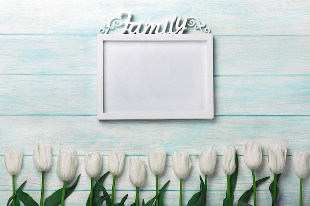 A bouquet of white tulips with a frame for inscription on blue boards Premium Photo