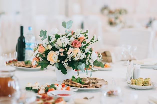 Букет из роз, эустомы и листьев эвкалипта. цветочное свадебное украшение. сервировка свадебного стола украшена живыми цветами. Premium Фотографии