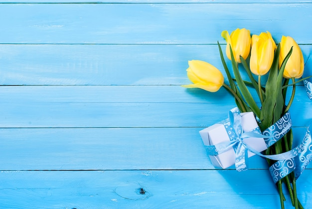 Bouquet of yellow tulips and a gift with a blue ribbon on a blue wooden background Premium Photo