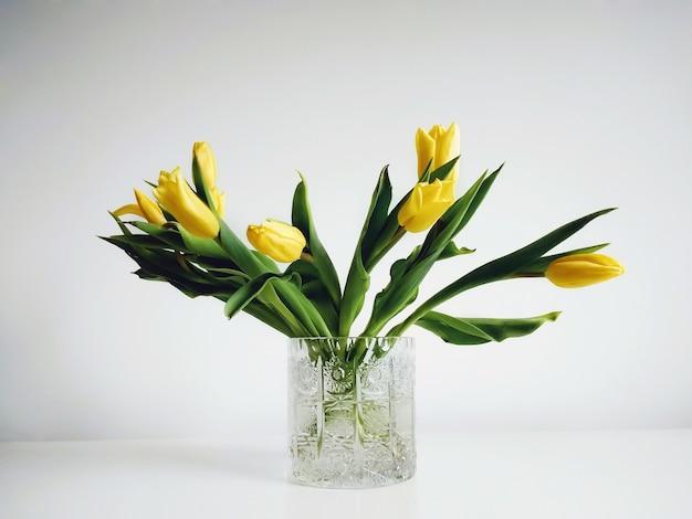 Bouquet di tulipani gialli in un vaso sotto le luci contro un bianco Foto Gratuite