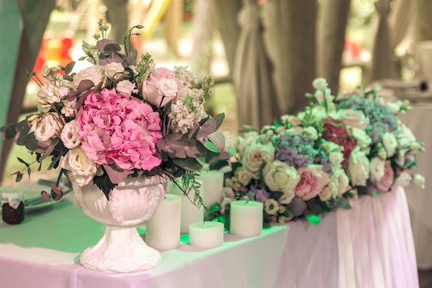 Bouquets of roses and eustoma and candles on decorated wedding table in rastuurant. Premium Photo