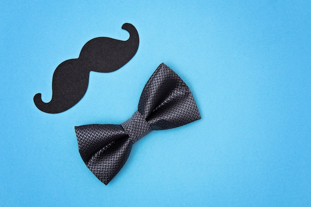 Bow tie and mustache on blue surface Premium Photo