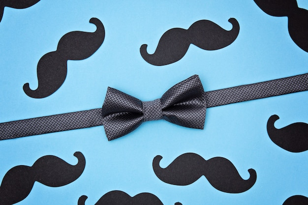 Bow tie and mustaches on blue surface Premium Photo