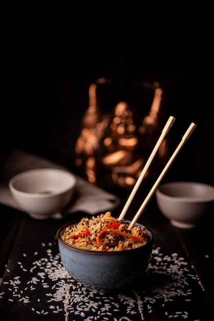 Bowl of asian food with rice and chopsticks Free Photo