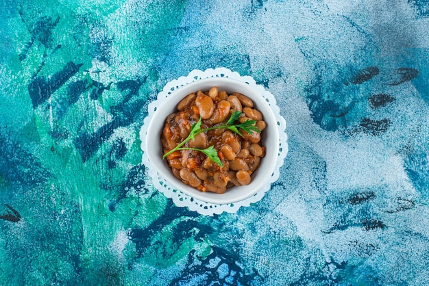A bowl of baked beans on coaster on blue. Free Photo