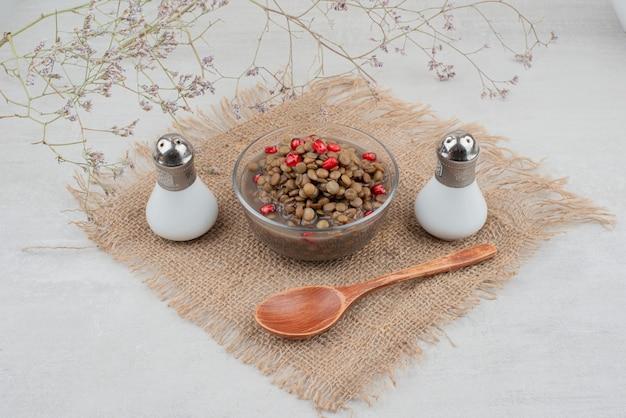 Ciotola di fagioli con semi di melograno e sale su tela Foto Gratuite