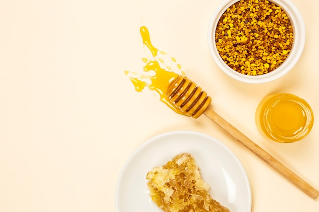 Bowl of bee pollen with honeycomb and honey jar Free Photo