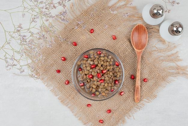 Ciotola di fagioli bolliti con semi di melograno e sale su tela. Foto Gratuite