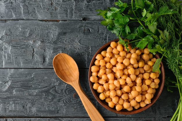 A bowl of boiled chickpeas, parsley and a wooden spoon on the rustic table. Premium Photo